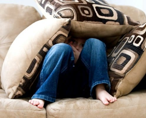 boy hiding in couch