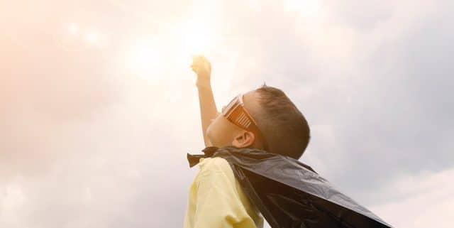 boy lifting hands to clouds