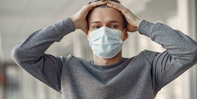 man-in-gray-sweater-covering-his-face-with-face-mask-3985172